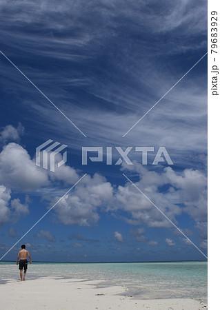 モルディヴの美しい浅瀬を散歩する日本人男性と空に浮かぶ芸術的な雲 79683929
