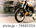 道路に咲いた可憐なオレンジ色の草花とバイク 79685354