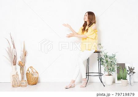白い壁に置いてある椅子に座って、案内のジェスチャーをする若い女性 79719879