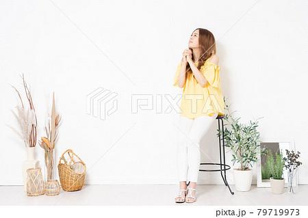 白い壁の前に置いてある椅子に座って、お願いをする若い女性 79719973