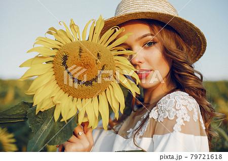 Beautiful and stylish girl in a field wirh sunflowers 79721618