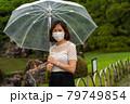 雨の中マスクをしている女性 79749854
