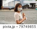 雨の中マスクをしている女性 79749855