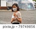 雨の中マスクをしている女性 79749856