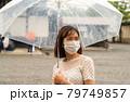 雨の中マスクをしている女性 79749857