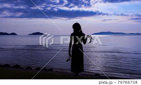 海辺でハイヒールを持って佇む女性 79766738