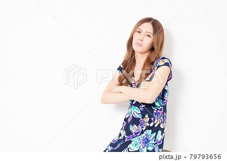 白い壁の前で考え事をする、青いワンピースを着た若い女性 79793656