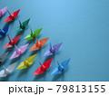 左下に集まるカラフルな折り鶴のグループと青背景のコピースペース 79813155