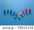 中央で下降線から上昇線を描くカラフルな折り鶴のグループ 79813158