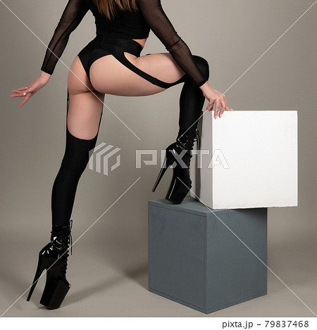 Beautiful female legs in black high-heeled shoes for pole dance. 79837468