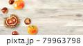 秋の食材:テーブルの上に転がる栗と柿の俯瞰水彩イラスト。バナー背景。 79963798