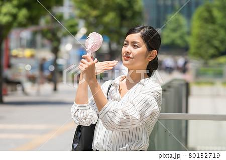 ビジネス街でミニ扇風機(ハンディファンを持つビジネスウーマン 80132719