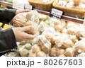 スーパーで玉ねぎを手に取る若い女性手元 80267603