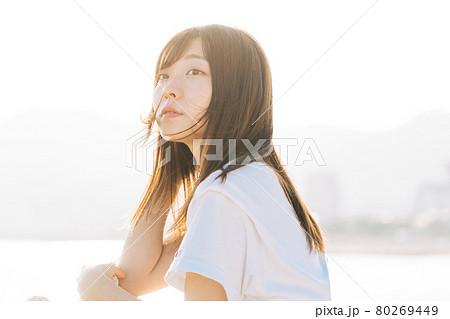 夕日に染まる海と若い女性  80269449