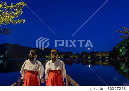 京都府京都市 大覚寺の観月の夕べで大沢池の遊覧船の到着を待つ二人の巫女さん 80297248
