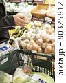 スーパーで玉ねぎを手に取る若い女性手元 80325812