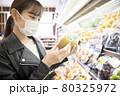 スーパーで買い物をする(キウイを選ぶ)若い女性買い物客 80325972