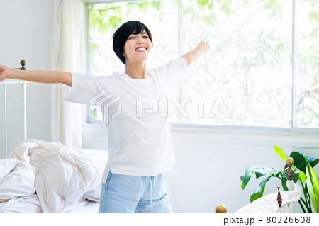 寝起きにベッドでストレッチをする若い女性 80326608