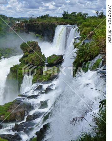 アルゼンチン・ブラジル国境エリアのイグアスの滝にてジャングルの間から流れ落ちる大量の水 80328597