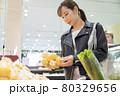 スーパーでみかんを手にする女性買い物客 買い物イメージ 80329656