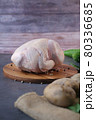raw whole chicken and vegetables on a chopping board  80336685