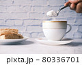 pouring white sugar in a tea cup  80336701