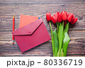 envelope and red tulip on table  80336719