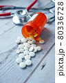 white color medical pills spilling on wooden table  80336728