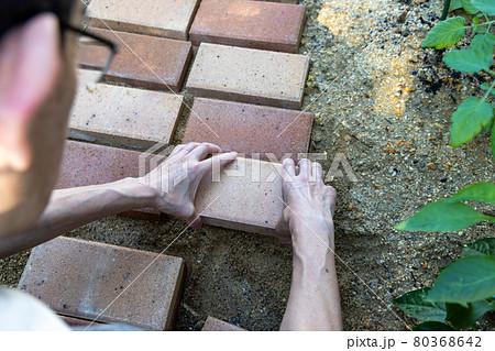 DIYで庭にレンガを敷いて小径を作っているところ 80368642