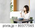 カフェでコーヒーを飲む若い女性 80377565