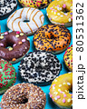 donuts with different flavors of icing on a blue 80531362