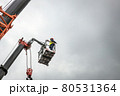 the automatic retractable boom of the crane and the foreman in the cradle of the crane manage 80531364