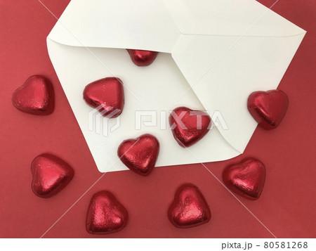 ハート型のチョコレートと白い封筒(赤背景・下向きにあふれるチョコ)、バレンタイン・ホワイトデーイメー 80581268