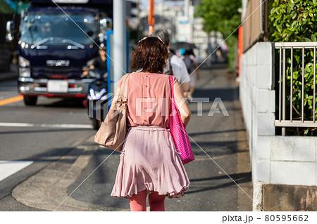 ピンクのバッグを持って足早に歩くピンクの服を着た女性 80595662