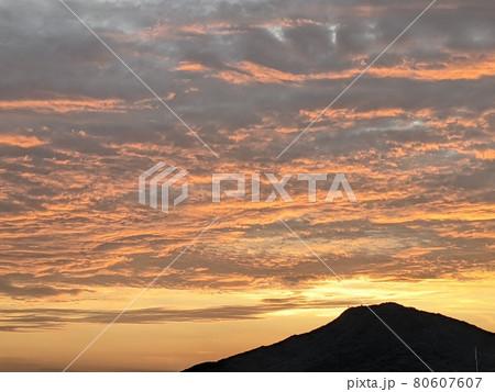 糸島富士と言われる可也山を黒いシルエットに浮かび上がらせて漂う筋雲を神秘的なオレンジ色のに染める夕日 80607607