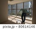 とても日当たりのいい新築マンションのリビングでカーテンの採寸をする中年男 80614146