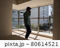 とても日当たりのよい新築マンションのリビングでスマホを使って電話する中年男 80614521