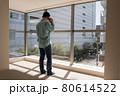 とても日当たりのよい新築マンションのリビングでスマホを使って電話する中年男 80614522