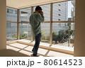 とても日当たりのよい新築マンションのリビングでスマホを使って電話する中年男 80614523