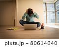住宅購入、賃貸、引っ越し、仕事等のトラブルで新築マンションのリビングで頭を抱える中年男性 80614640