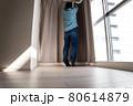 新築マンションのリビングにカーテンをかける中年男性 80614879