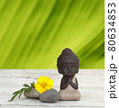 Little Buddha meditating with stones and bamboo on wooden background 80634853