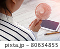 Young Asian woman with portable fan at workplace. Summer season. 80634855
