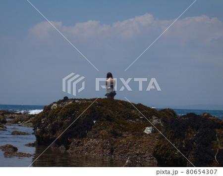 葉山真名瀬の磯で黄昏れる女性の後ろ姿 80654307
