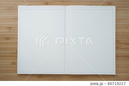 木目調の机に置かれた真っ白なノートブックの見開き 80719227