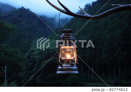 鹿の角ハンガーに掛けられたハリケーンランタンを灯す雨上がりの日没 80774623