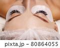 Eyelash Extension Procedure. Woman Eye with Long Eyelashes. Close up, selective focus. 80864055