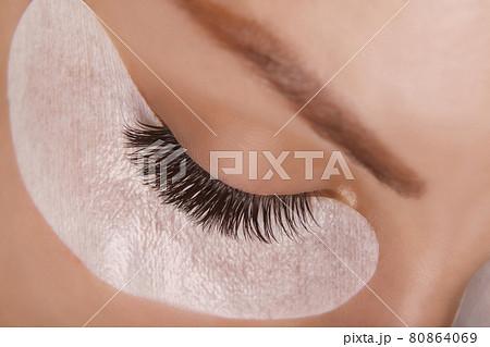 Eyelash Extension Procedure. Woman Eye with Long Eyelashes. Close up, selective focus. 80864069