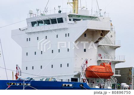 荷役中の商船の白い船橋とオレンジ色の閉囲型救命艇 80896750