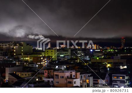 煙突が雲を吐き出すように見える夜の街 80926731
